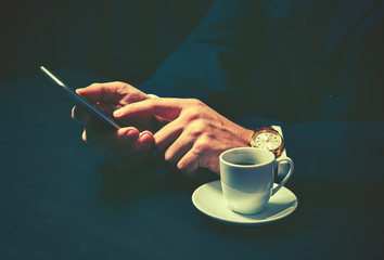 phone and a cup of coffee in hands of businessman