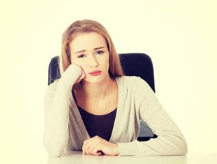 Sad worried woman sitting by a desk.