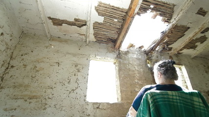 Senior person in ruined house looking out the window