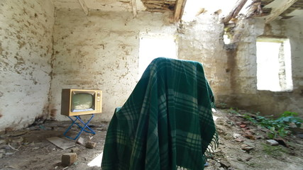 Old TV and empty chair in abandoned house