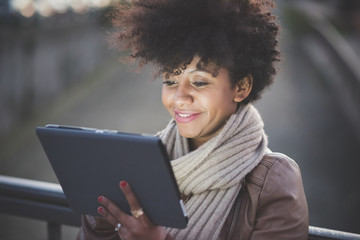 beautiful black curly hair african woman using tablet