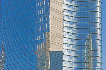 office building with glass facade and blue sky reflection