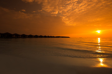 Beautiful sunset at tropical resort with overwater bungalows