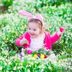 Beautiful little girl on Easter egg hunt in flower's meadow