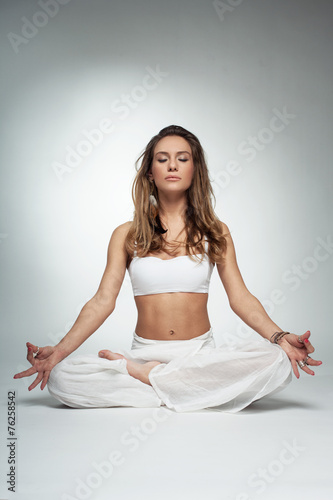 Young woman in yoga pose in studio on white background