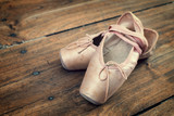 Fototapety Old pink ballet shoes on a wooden floor, vintage process