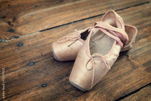 Old pink ballet shoes on a wooden floor, vintage process - 76259323