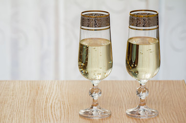 Two champagne flute filled with champagne.