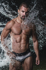 Muscled male torso in water