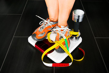 A pair of female feet standing on a bathroom scale with dumbbell