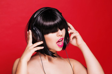 Woman listening to music on headphones enjoying a dance. Closeup