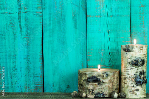 Log candles and acorns by teal blue wood background - 76263336