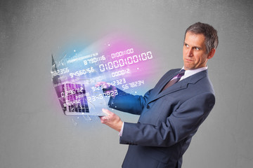 Businessman holding notebook with exploding data and numbers