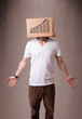 Young man gesturing with a cardboard box on his head with diagra