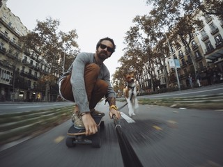 Man rides his skateboard followed by his dog