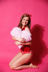 Happy woman with heart-shaped pillow