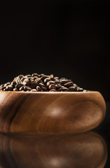 Brown Wooden Bowl Filled with Coffee Beans. Isolated Over Black