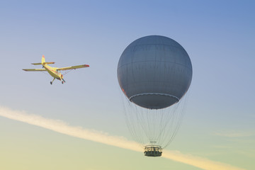 Gas Balloon and Yellow Aircraft against the Sky