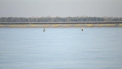 Two winter fishermen walking on frozen water storage reservoir