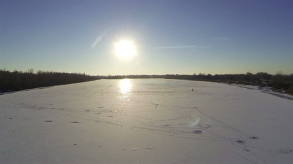 Flight over frozen river in winter with beautiful sun. Aerial