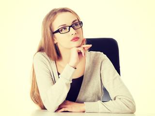 Beautiful thoughtful woman in eyeglasses sitting.