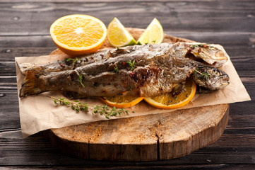 Baked trout fish with orange and thyme