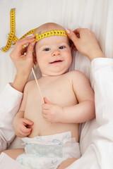 Kinderaerztin misst Kopfumfang eines Babys Ausschnitt