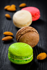 Colorful French macaroons on a dark rustic wooden background,