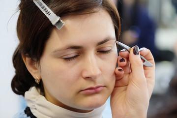 Makeup artist stylist applying with brush cosmetic on eyebrow