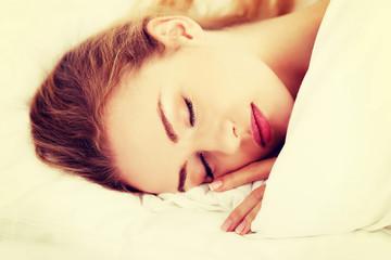 Sleeping woman lying in bed