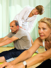 Yoga instructor showing asana to mature couple