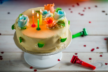 Sweet birthday cake with lighted candles and marzipan roses