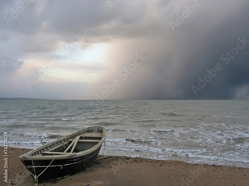 Plakat Lonely boat on the shore of a stormy sea