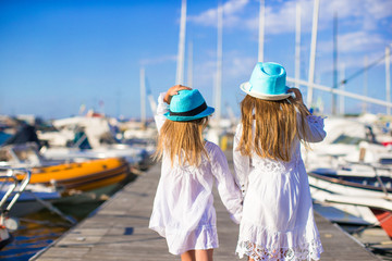Adorable little girls walking in a port during summer vacation