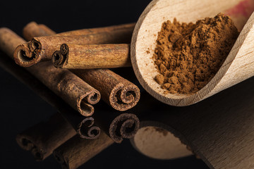 Cinnamon sticks and wooden spoon on dark reflective background