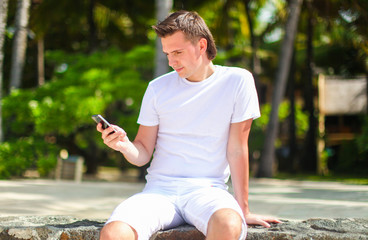 Young man talking on phone during tropical beach vacation