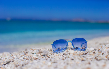 Close up of colorful blue sunglasses on tropical beach