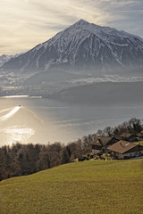 Sunrise in a village over the Thun lake in Swiss Alps in winter