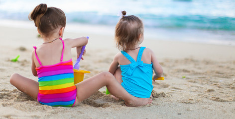 Adorable little girls playing with beach toys during summer