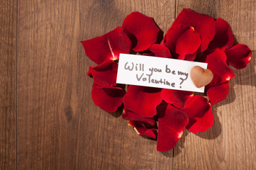 Message in rose petals on wooden background