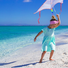 Little happy girl playing with flying kite on tropical beach