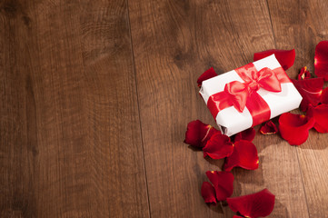 Present box in rose petals on wooden background