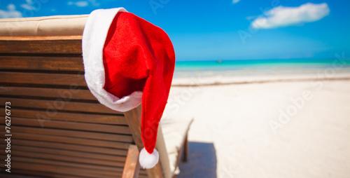Leinwanddruck Bild Red santa hat on chair longue at tropical caribbean beach