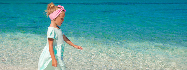 Adorable little girl having fun during beach vacation