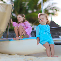 Adorable little girls have fun on white beach during vacation