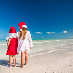 Little adorable girls in Santa hats during beach vacation