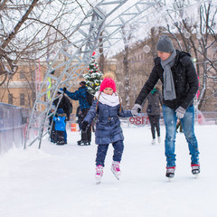 Adorable little girl and happy father on skating rink outdoor
