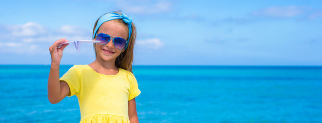 Happy little girl with paper airplane on white sandy beach