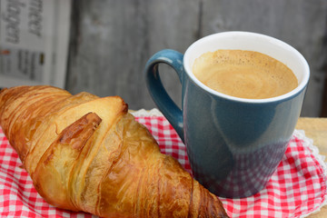 Coffee with croissant on old wooden table and newspaper