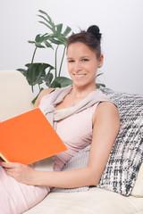 Junge Frau sitzt mit Buch auf dem Sofa mit Blick in die Kamera